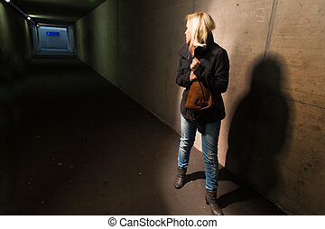 woman in the tunnel is afraid - a young woman in an...