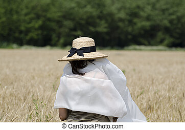 Woman in the wheat field with a sheet