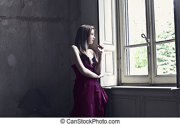 woman in the window - beautiful woman looks out the window