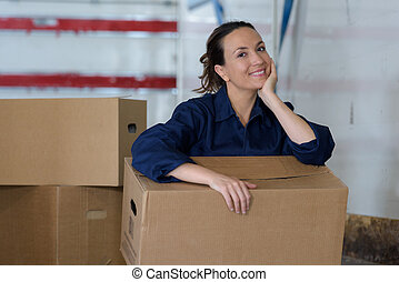 woman in the workplace holding a large cardboard box
