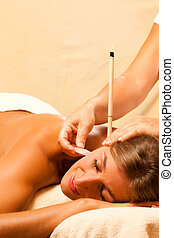 Woman in therapy with ear candles
