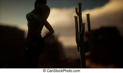 woman in torn shirt standing by cactus in desert at sunset