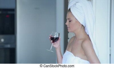 Woman in towel drinking wine