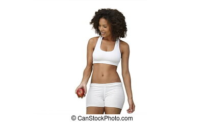 Woman in training clothes throws and apple upwards against a...