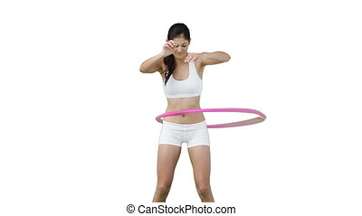 Woman in training clothes using a hula hoop against a white...