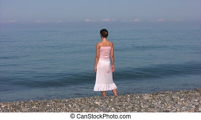 woman in transparent skirt stands on beach