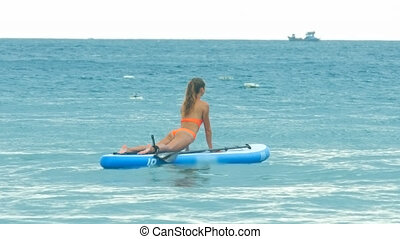 woman in Upward-Facing Dog on paddle board in ocean
