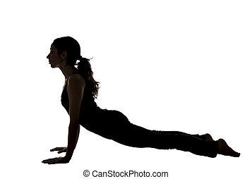 Woman in Upward Facing Dog pose in Yoga in Silhouette