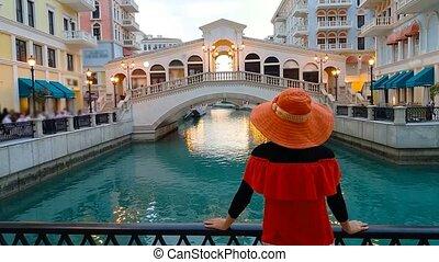 Woman in Venice Doha twilight - Back of woman on balcony...