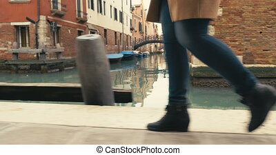 Woman in Venice walking along the canal