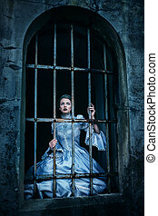 Woman in victorian dress imprisoned in a dungeon