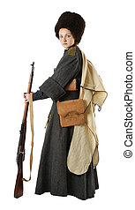 Young woman is wearing vintage uniform of Russian foot Cossack in time First World War. She is member of Historical Reenactment. Russian Cossack is standing. Re-enactor is dressed in woolen greatcoat, fur cap and hood. She has bags and a rifle.