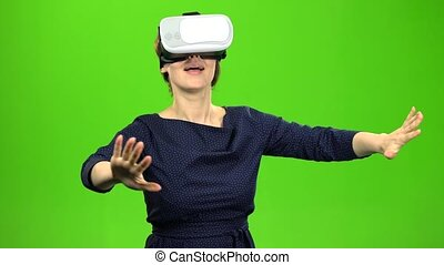 Woman in virtual glasses is watching an interesting film....