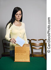 Woman in voting booth - A young woman with a voter in the...