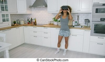 Woman in VR glasses dancing in kitchen - Young ethnic model...
