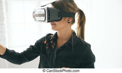 Woman in VR headset looking up and trying to touch objects...