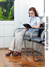 Woman In Waiting Room - Full length of a young woman reading...
