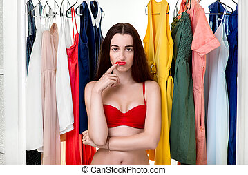Woman in wardrobe - Young woman in underwear thinking what...