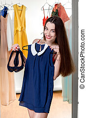 Woman in wardrobe - Young happy woman trying on new blue ...
