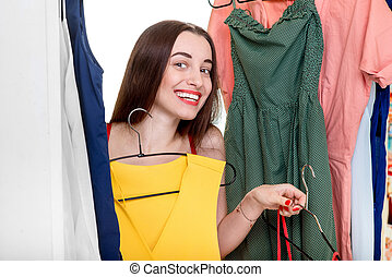 Woman in wardrobe - Young happy woman trying on new dress to...