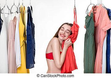 Woman in wardrobe - Young woman in underwear looking through...