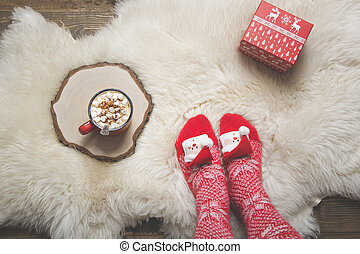 Woman in warm christmas knitted socks wants to drink coffee and open a gift. Top view.