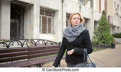 woman in warm clothes and scarf walking down the street.