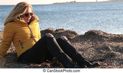 Woman in warm clothing sitting on winter beach