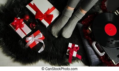 Woman in warm cozy socks sits on a gray fur skin near a retro turntable. Presents, jewelry and tinsel are spread around. Festive mood. Merry christmas and new year. Close up. Slow motion
