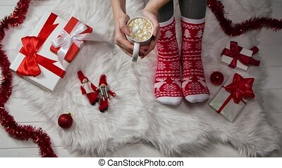 Woman in warm red white socks with an ornament sits on a fur skin around boxes with gifts and New Years decorations. Hands hold a cup of hot chocolate with marshmallows. The concept of a cozy happy holiday at home. Close up. Slow motion.