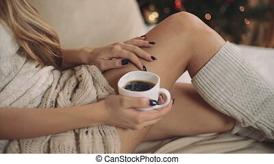 woman in warm sweater on the bed with cup of coffee in hands, Christmas tree new year closeup hands
