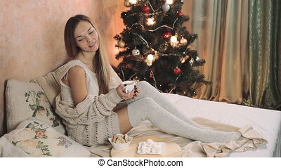 woman in warm sweater on the bed with cup of coffee in hands, Christmas tree new year