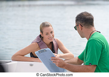 Woman in water looking at notes held by man in boat