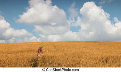 woman walks on a field of wheat against a blue sky