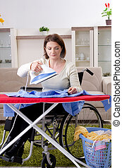 Woman in wheelchair ironing at home