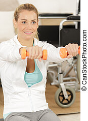 woman in wheelchair lifting weights