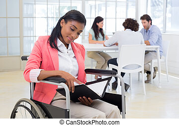 Woman in wheelchair reading document with colleauges in background in the office