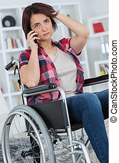 woman in wheelchair using her smartphone