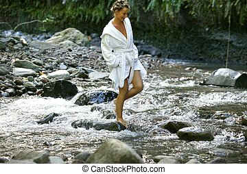 Woman in white bathing gown walking down stream