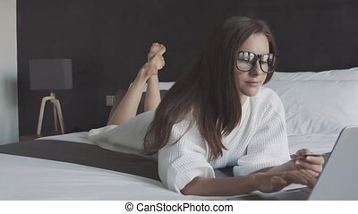 Woman in white bathrobe and glasses bue ticket with credit card and laptop, lie on the bed.