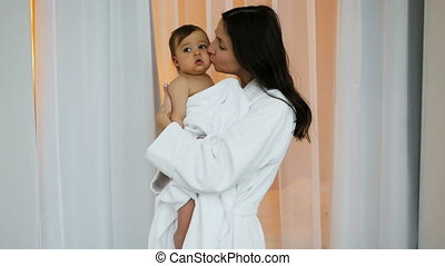 woman in white Bathrobe holding son in her arms