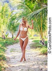Woman in white bikini posing between palm trees at the tropical beach