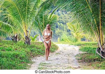 Woman in white bikini walking between palm trees at the tropical beach