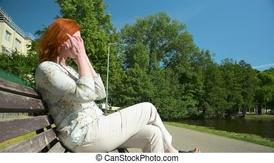 Woman in white casual clothes with red hair sits on the bench near the pond
