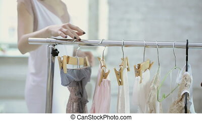 Woman in white clothing comes to rack with hangers to choose clothes