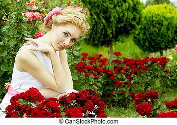 Woman in white dress among rose garden