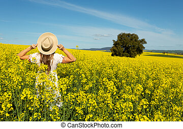 Woman in white dress in field of golden canola
