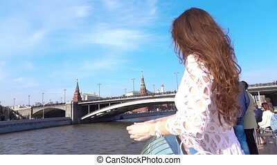 Woman in white dress looking at Moscow Kremlin from the river tour boat. Travel to Russia concept. Slow motion video