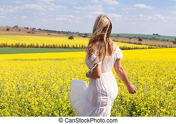 Woman in white dress looking out over fields of golden canola