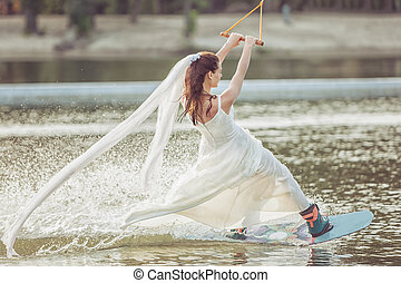 Woman in white dress on a water ski.